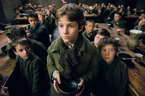 Image from Roman Polanski's film, <em>Oliver Twist</em> (2005) showing Oliver holding a bowl.