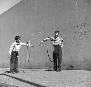 Two young boys are spinning hoops around their arms.